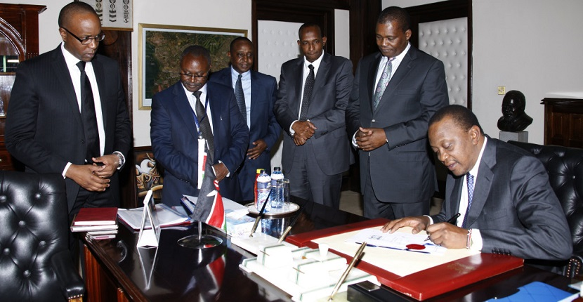 President Uhuru Kenyatta signs the 2014 Value Added Tax (VAT) and Pubilc Finance Management ammendment Acts into law at State House, Nairobi. Looking on from left is   Solicitor General Njee Muturi, Clerk of the National Assembly Justin Bundi, Cabinet Secretary National Treasury Henry Rotich, Majority Leader Aden Duale and Speaker of National Assembly Justin Muturi.