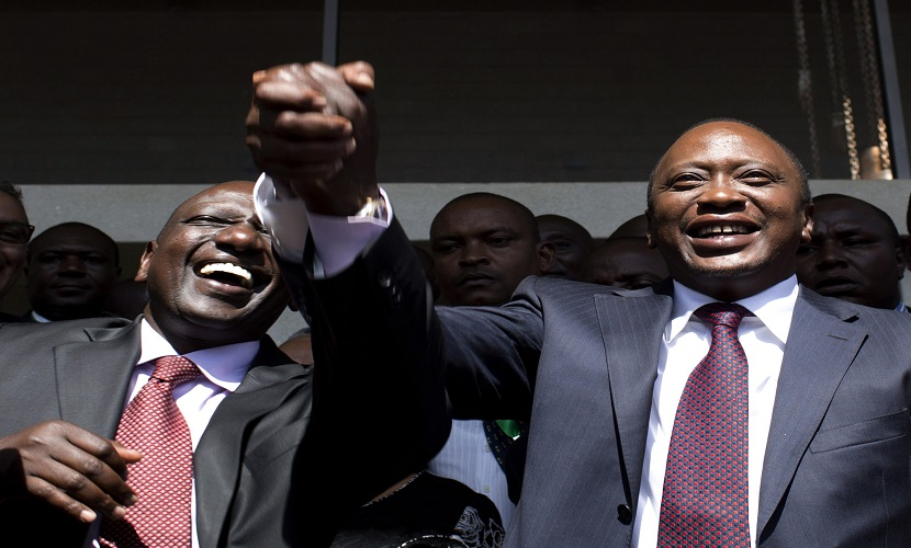 President-elect Uhuru Kenyatta (R) greets his supporters with his running mate, former cabinet minister William Ruto after attending a news conference in Nairobi March 9, 2013. Kenyatta, indicted for crimes against humanity, was declared winner of Kenya's presidential election on Saturday with a tiny margin, just enough to avoid a run-off after a race that has divided the nation along tribal lines. REUTERS/Siegfried Modola (KENYA - Tags: ELECTIONS POLITICS)